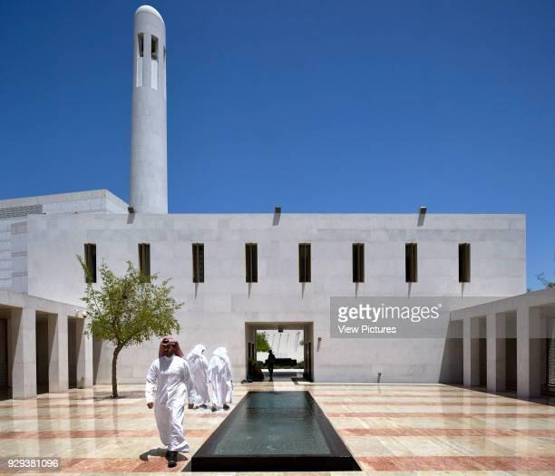 Mosque courtyard midday prayers with minaret. Jumaa Mosque, Doha, United Arab Emirates. Architect: John McAslan & Partners, 2017.