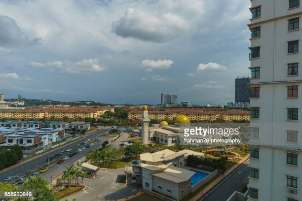 mosque in between condominium block - shah alam stock photos and pictures