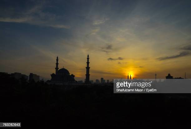 Mosque In City Against Sky During Sunset