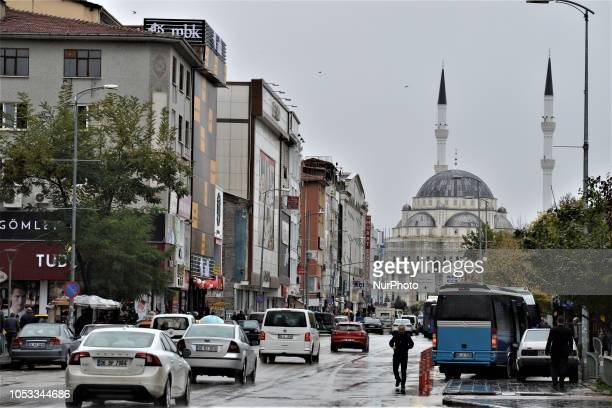 A mosque is silhouetted as pedestrians walk on a crowded street during a rainy day in the autumn season in Ankara Turkey on October 25 2018