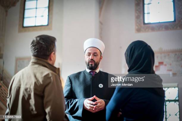 mosque man talking with people - イマーム寺院 ストックフォトと画像