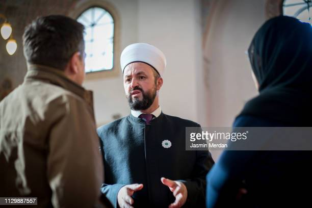 mosque man talking with people - imam stock photos and pictures