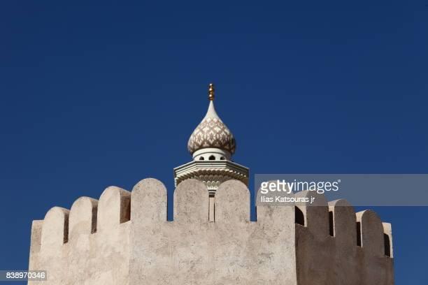 Mosque minaret behind tower of sandstone Nizwa fort in Oman