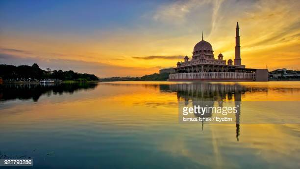 Mosque Reflecting On Calm Lake Against Sky At Sunset