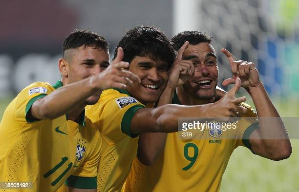 Mosquito and Boschilia of Brazil celebrate with a teammate after scoring a goal during their FIFA U17 World Cup 2013 football match against Slovakia...