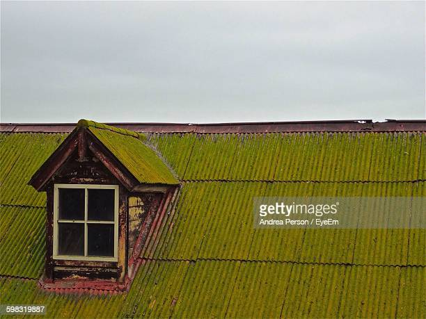 Moss Covered House Roof Against Clear Sky