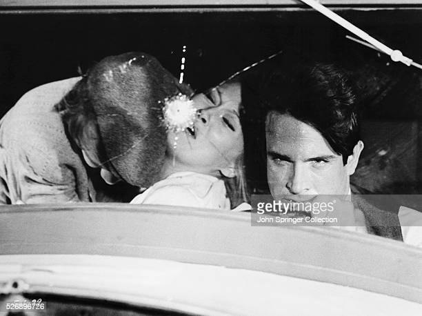 CW Moss slumps over Bonnie Parker after being shot in a getaway car driven by Clyde Barrow in the 1967 film Bonnie and Clyde
