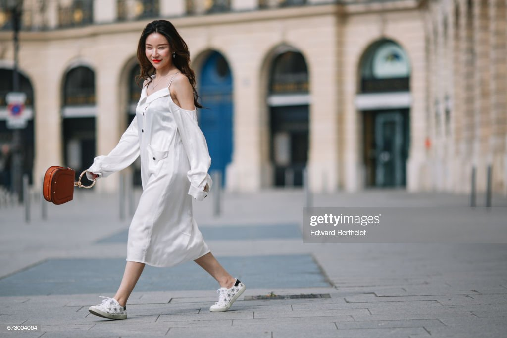 Moss Xu wears a white dress, white sneakers with embroidered stars, and a Chloe brown bag, at Place Vendome, on April 23, 2017 in Paris, France.