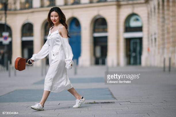 Moss Xu wears a white dress white sneakers with embroidered stars and a Chloe brown bag at Place Vendome on April 23 2017 in Paris France