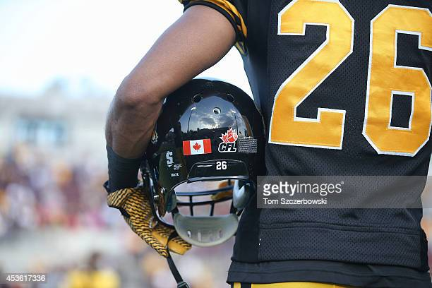 Mossis Madu of the Hamilton TigerCats holds his helmet as he stands for the playing of the Canadian anthem before the start of CFL game action...