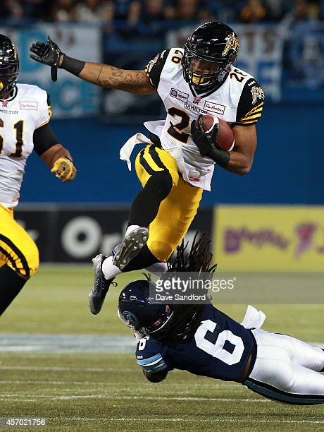 Mossis Madu of the Hamilton TigerCats leaps over an attempted tackle by Alex Suber of the Toronto Argonauts during their game at Rogers Centre on...