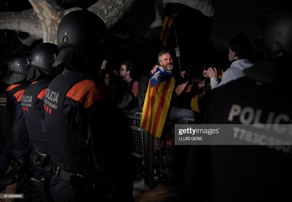 'Mossos D'Esquadra' officers (Catalan regional police) stand in front of demonstrators during a demonstration outside the Catalan parliament on January 30, 2018 in Barcelona. The speaker of Catalonia's parliament Roger Torrent delayed a key debate in the regional assembly on ousted separatist leader Carles Puigdemont's bid to form a new government, but defended his right to return to power. /
