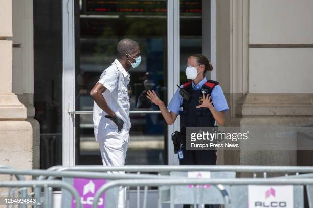 Mossos d'Esquadra police officer is seen talking to a man at the train station of Lleida, capital of the Segrià region, on July 6, 2020 in Lleida,...
