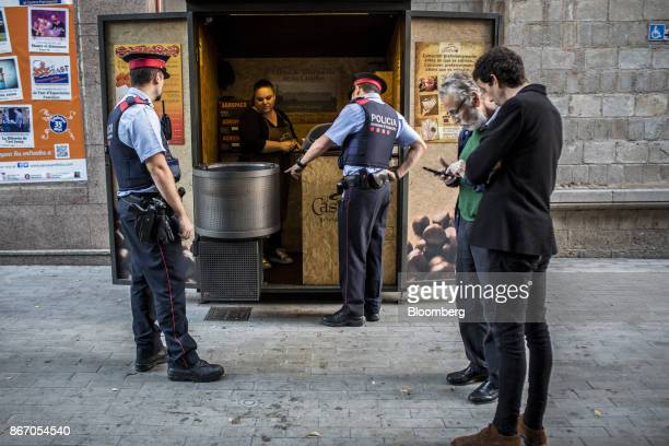 Mossos d'Esquadra police officers from the Citizen Security Unit speak to a street trader while on patrol in the Sant Feliu de Llobregat district of...