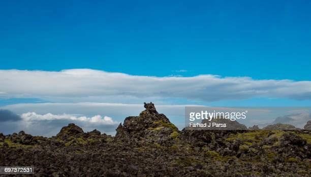 Mossy rocks under a partly cloudy sky.