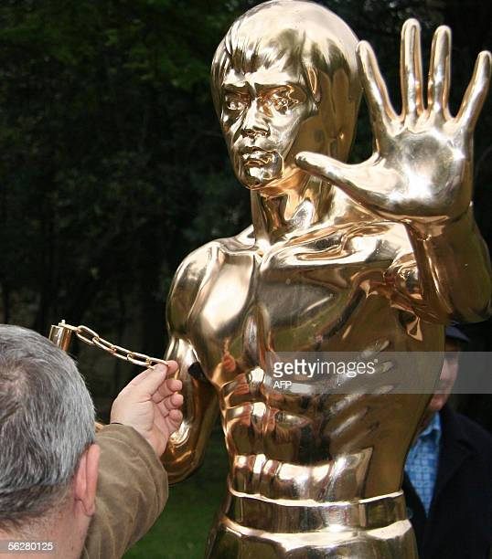 A resident of the southern Bosnian town of Mostar shows the broken part of the statue of late martial arts actor Bruce Lee 27 November 2005 after the...