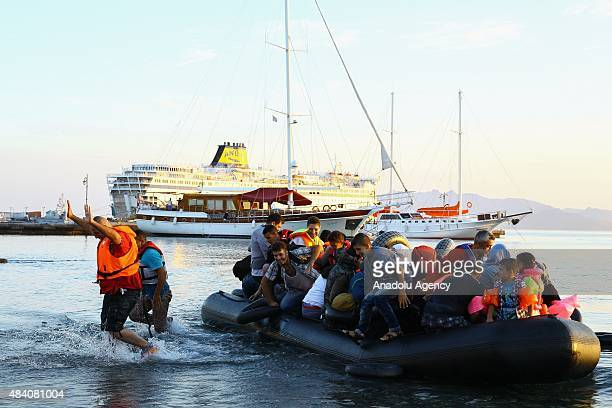 Mostly Syrian refugees and migrants celebrate upon arrival on the Greek island of Kos after crossing a part of the Aegean Sea between Turkey and...