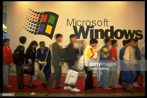 Mostly youthful consumers lined up by US Microsoft Windows 95 exhibit sign re US cos for trade investment