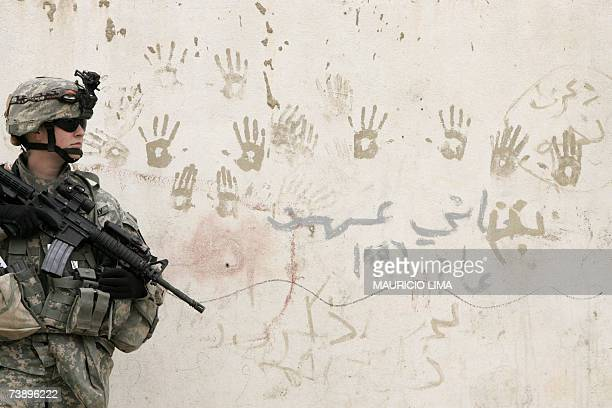 A US female soldier from Alpha Company 2nd Battalion 7th Cavalry Regiment secures the area during a joint housetohouse search operation between Iraqi...