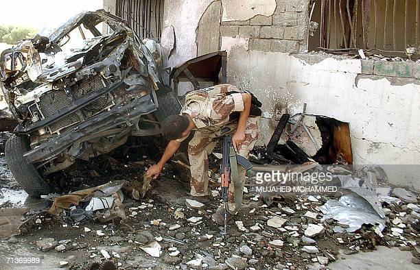 An Iraqi police commando inspects the area where a suicide car bomb exploded near a police station in the northern city of Mosul 05 July 2006 A...