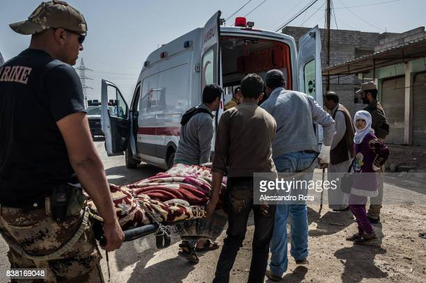 IRAQ Mosul West 12 Mar 2017 A civilian injured during the fighting is dragged into an ambulance outside the frontline clinis in Mansor neighboorhood...