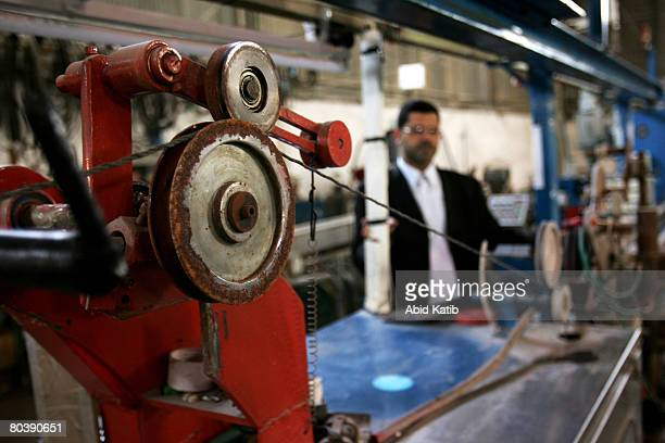 Mo'taz AlHaddad one of AlHaddad factory's owners inspects corrosion and the machine which are not currently being used at the electrical components...