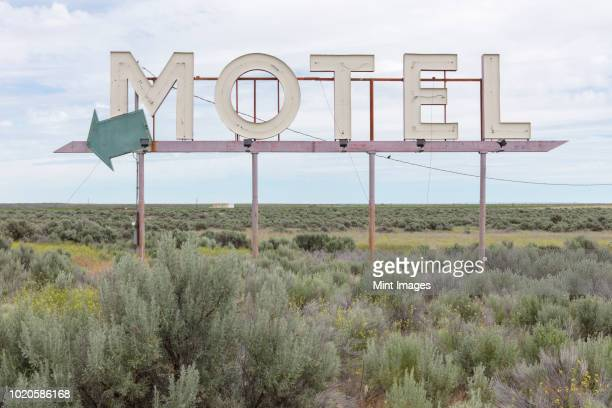 motel sign in field of sage brush, out of context - prairie stock photos and pictures