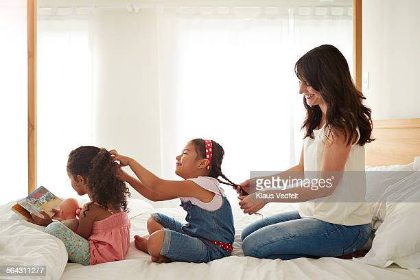 Mother & 2 kids doing each others hair on a row