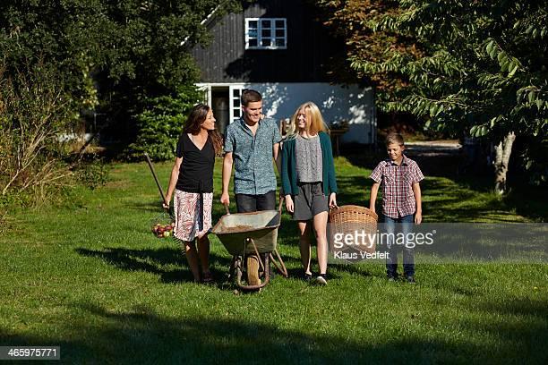 Mother & 3 kids walking togther in garden