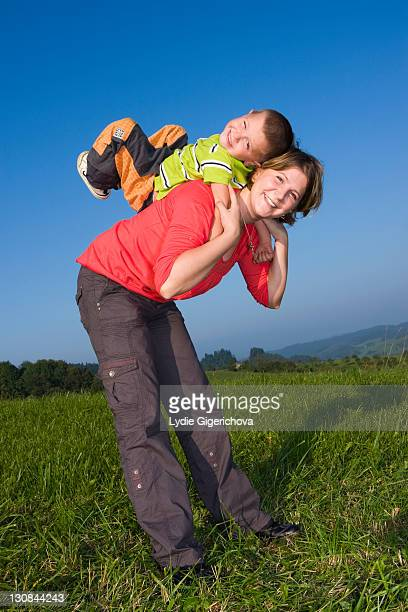 mother, 30 years, and son, 6 years, playing in a meadow - 20 29 years stockfoto's en -beelden