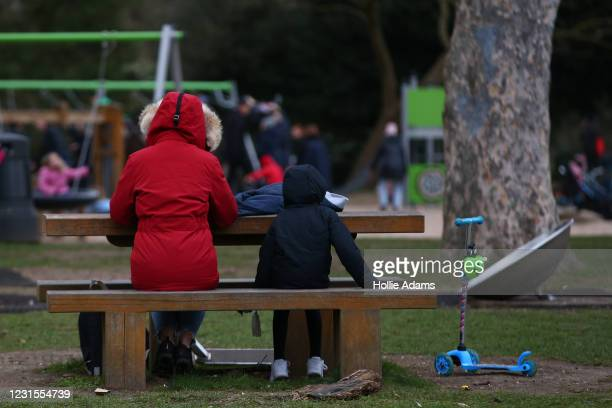 Mother a child sitting on a bench at Victoria Park playground on March 6, 2021 in London, England. Londoners are enjoying bright weather as end of...