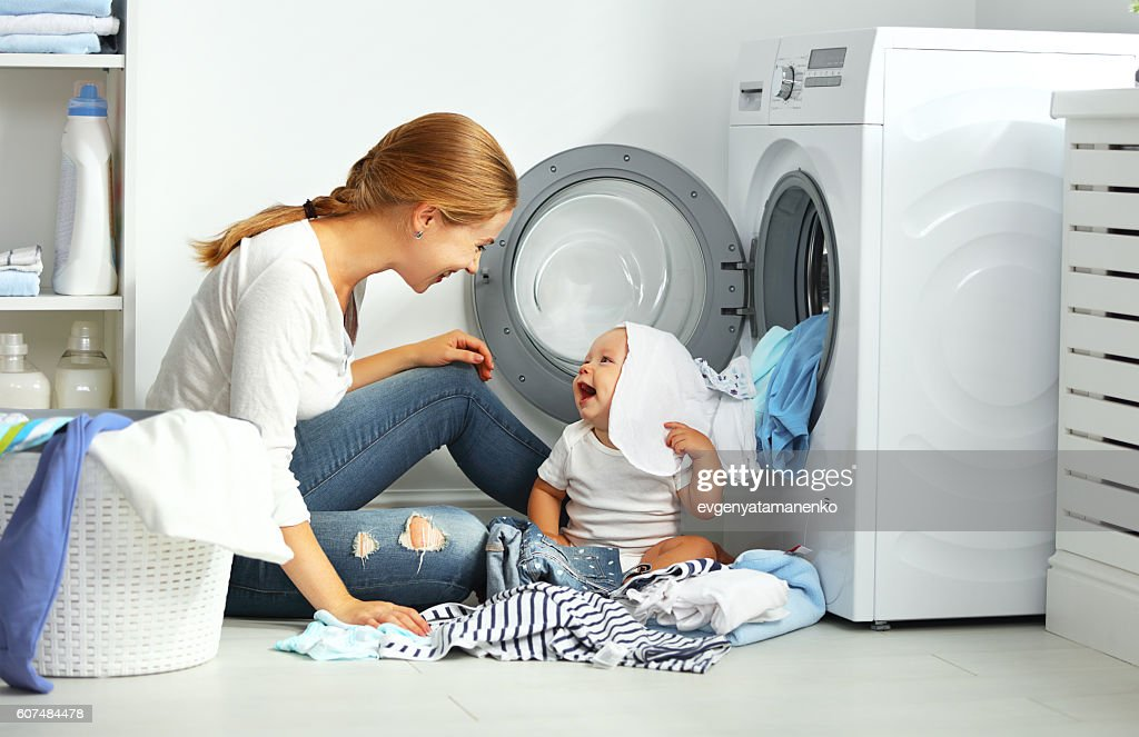 mother a housewife with a baby fold clothes