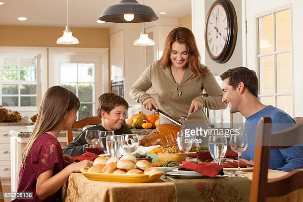 Mother About To Carve Into Thanksgiving Turkey At Diinner Table