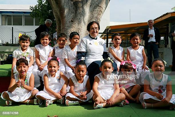 Mother Adela, wearing the german football jersey, pose next to children during the DFB Delegation visit to Casa de Cuna celebrating the 30th...