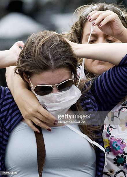 STORY A mother adjust a mask to her daughter as they wait to receive medical attention in Rio de Janeiro on July 23 2009 Authorities said the number...