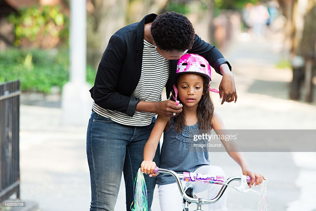 Mother adjusting daughter's bicycle helmet : Stock Photo