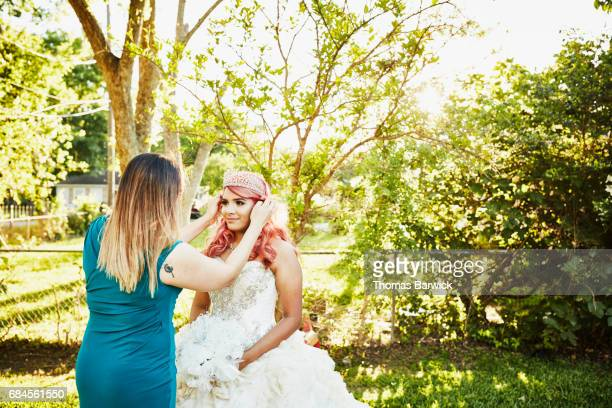 mother adjusting daughters hair in backyard before quinceanera - 14 15 anni foto e immagini stock