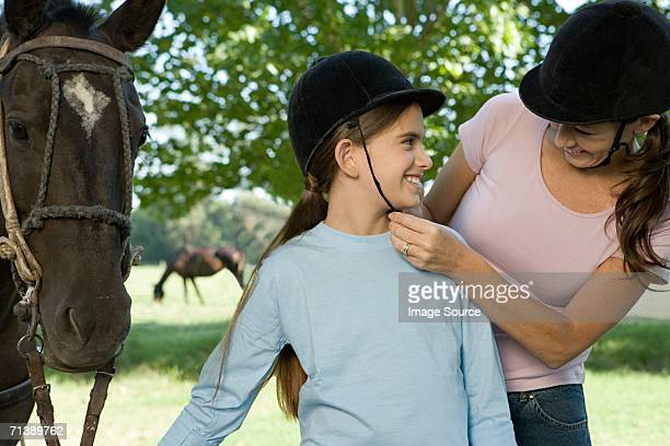mother adjusting daughter's riding hat - riding hat stock pictures, royalty-free photos & images