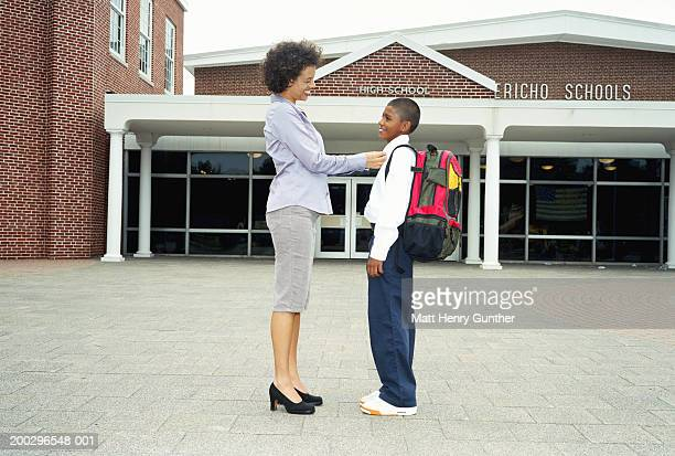 mother adjusting son's collar outside school, smiling, side view - kragen stock-fotos und bilder