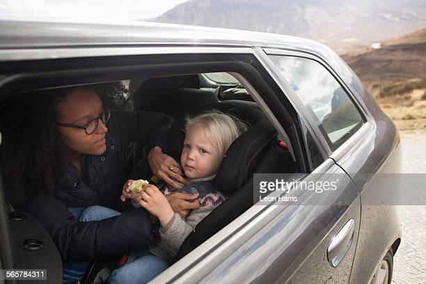 Mother adjusting sons seatbelt in car