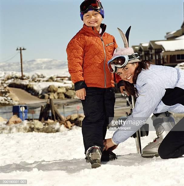 Mother adjusting son's (4-6) ski boot, smiling, portrait