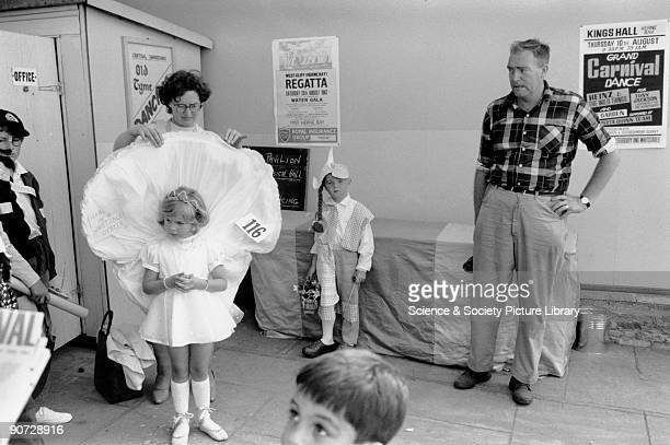 A mother adjusts her daughter's fancy dress while other children and a bemused man look on Photograph taken at Herne Bay Kent Photographer Tony...