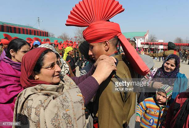 A mother adjusts the uniform of her son after he was inducted as a soldier in the Jammu and Kashmir Light Infantry Regiment march during a passing...