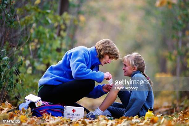 mother administering first aid to daughter - kids first aid kit stock pictures, royalty-free photos & images