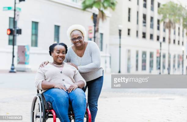 mother, adult daughter with spina bifida, in city - of deformed people stock pictures, royalty-free photos & images