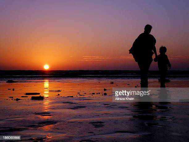 Mother along her child having a walk and wittnessing the sunset over the seashore of Sea view beach, Karachi, Pakistan.