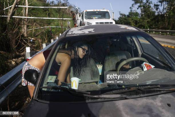 Mother Anais Rivera leans into her car holding her three children after bathing and washing clothes with water funneled into pipes from a mountain...