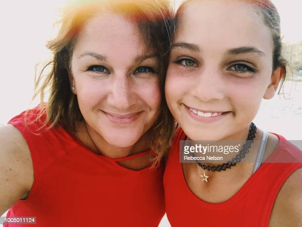 Mother and 11 year old daughter taking selfie at sunset on the beach