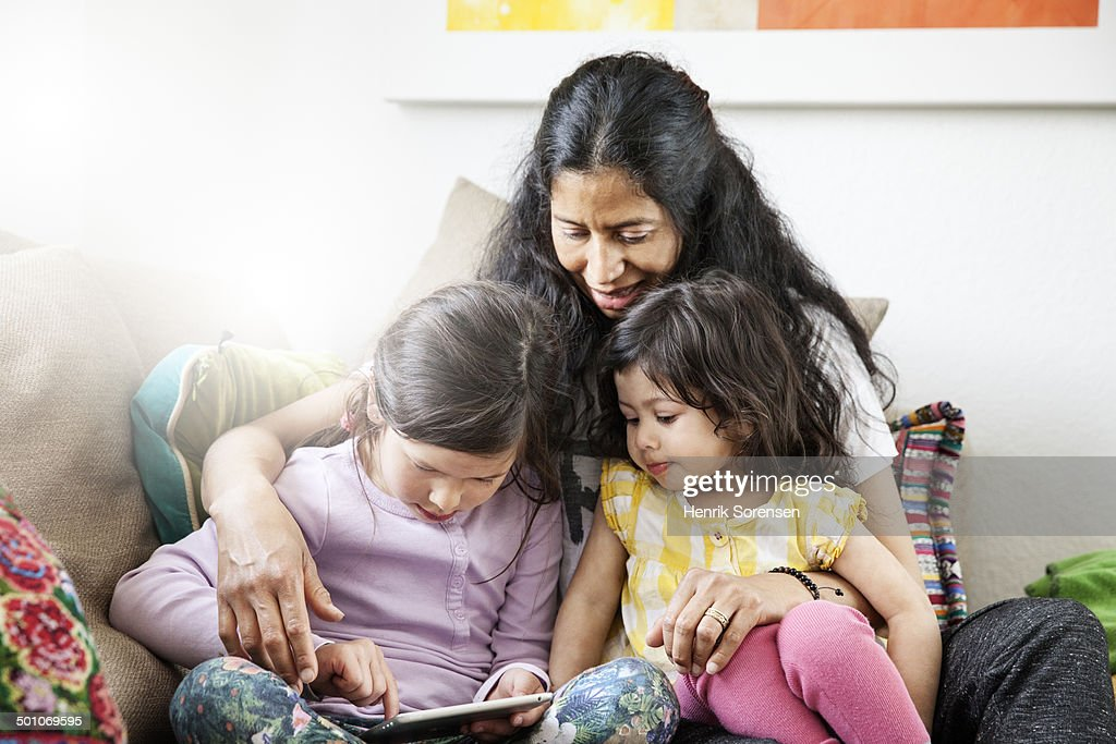Mother and 2 young daughters playing with a tablet, sitting in a couch