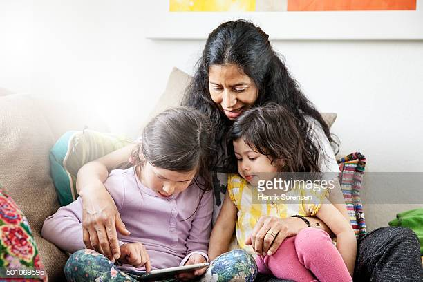 Mother and 2 daughters playing with a tablet